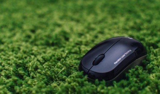 Ratón de ordenador abandonado sobre un paisaje de césped verde.