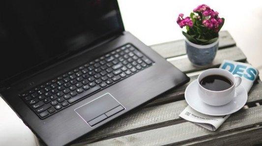 Taza de café junto a un ordenador y una revista.