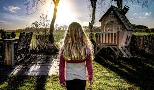 Niña contemplando el atardecer junto a una casa de madera.