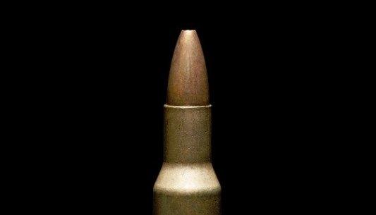 Primer plano de una bala  dorada con un fondo negro.