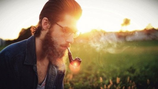 Joven barbudo fumando en pipa al atardecer.