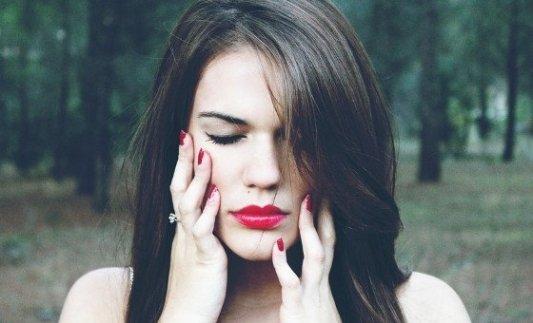 Joven mujer pálida con los labios muy pintados frente a un bosque.