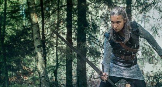 Joven guerrero elfo empuñando una espada en los bosques.
