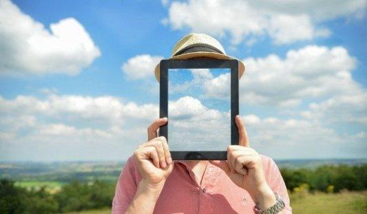 Persona frente a un paisaje de cielo y nubes con una tableta transparente sobre la cara