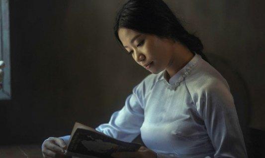 Joven mujer leyendo un libro en una habitación de luz suave.