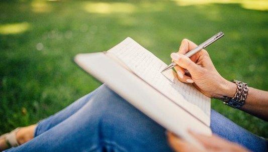 Mujer escribiendo a mano en un cuaderno sentada en un jardín