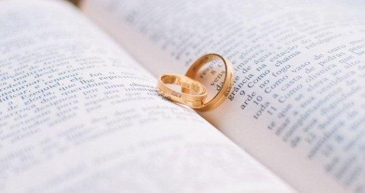 Dos alianzas de matrimonio sobre un libro abierto por la mitad.