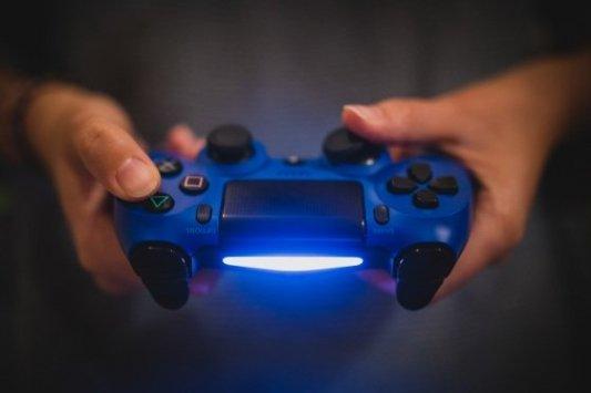 Mando iluminado con led azul de una consola Playstation.