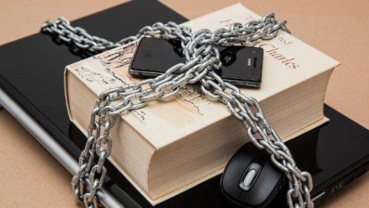 Libro atado con cadenas a un teléfono y un portátil.