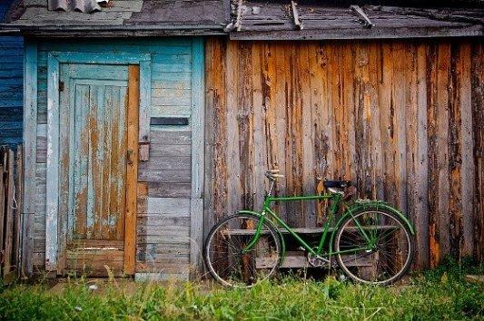Bicicleta apoyada sobre una casa de madera