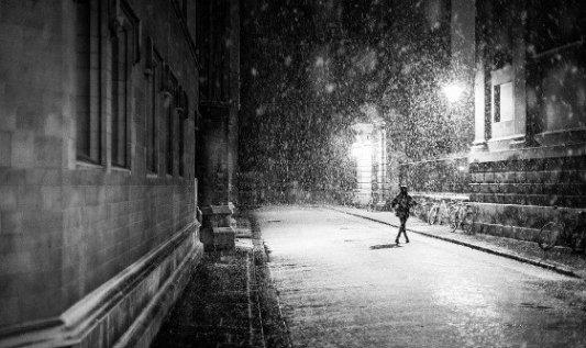 Persona caminando bajo el nieve en medio de una ciudad antigua.