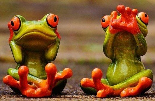 Dos ranas de cerámica, una se tapa los oídos y la otra la boca.