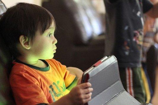 Niño pequeño leyendo con una tableta en las manos.