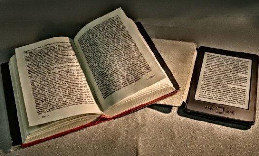 Viejo libro impreso junto a un ereader con funda de cuero.