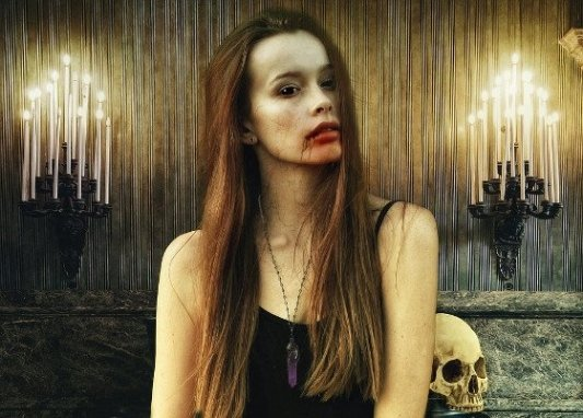 Vampira con la boca llena de sangre junto a dos candelabros.