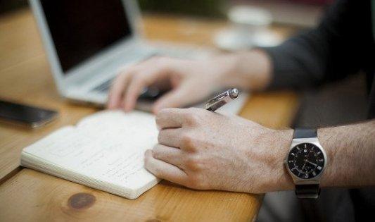 Escritor anotando en un bloc con ordenador al fondo.