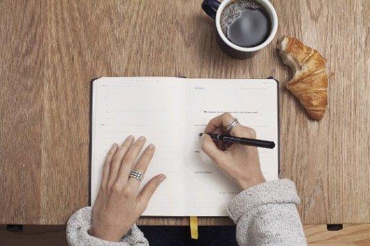 Mujer escribiendo en un cuaderno con café y cruasán.