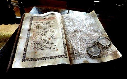 Libro antiguo iluminado junto a unas viejas gafas redondas.