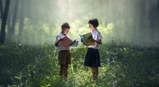 Dos niños leyendo en el bosque.