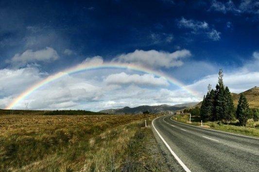 Carretera con arco iris al fondo.