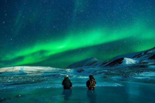 Dos exploradores en el Ártico mirando una aurora boreal.