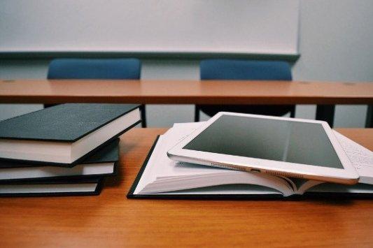 Libros de texto y una tablet en un aula.