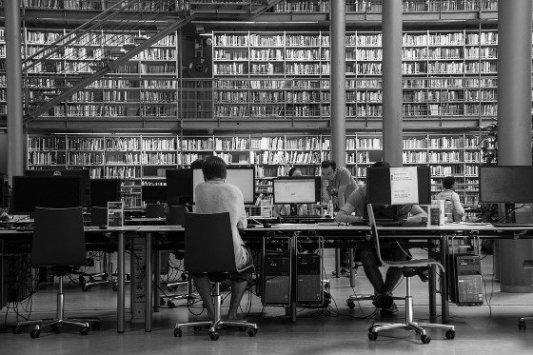 Biblioteca con estudiantes y ordenadores.