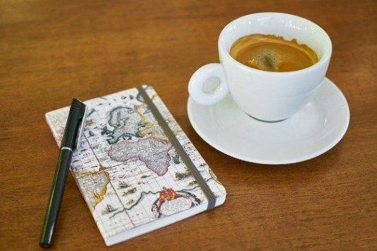 Bloc de notas con bolígrafo y un café.