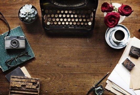 Máquina de escribir con cámara de fotos y flores.
