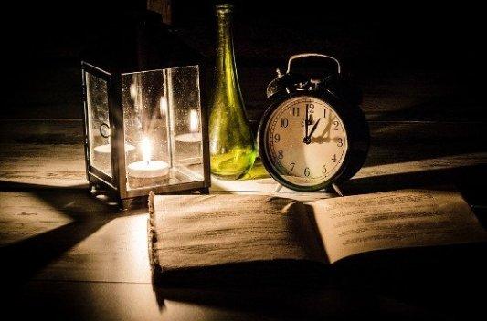 Libro, vela encendida y reloj.