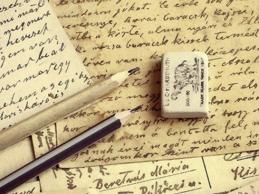 Dos lápices, goma de borrar y papeles escritos a mano.