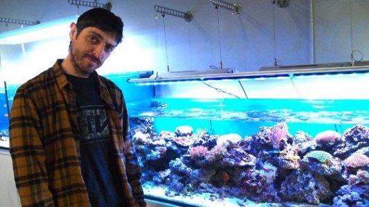 Emilio Bueso junto a un acuario con caracoles.
