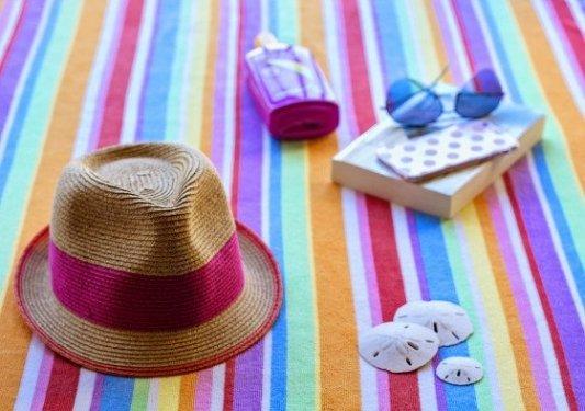 Sombrero, toalla, gafas de sol y un libro en la playa.