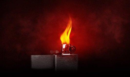 Encendedor tipo Zippo con una llama rojiza.