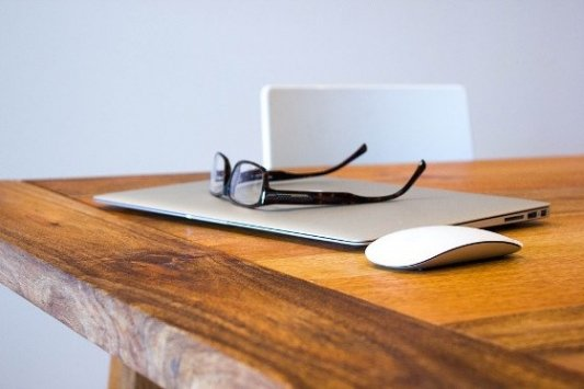 Mesa con máquina de escribir, café, gafas y cámara.