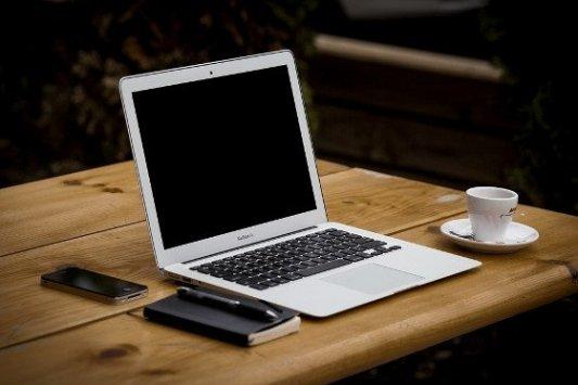 Ordenador, libro de notas y café.