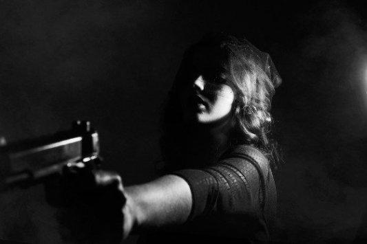 Mujer en la oscuridad con una pistola.