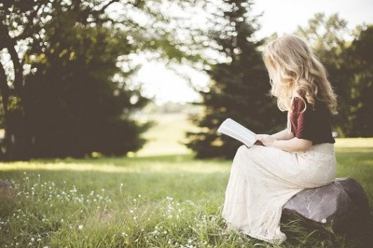 Chica joven leyendo un libro en el campo.