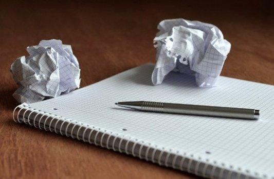 Bloc de notas en blanco con bolas de papel arrugadas.