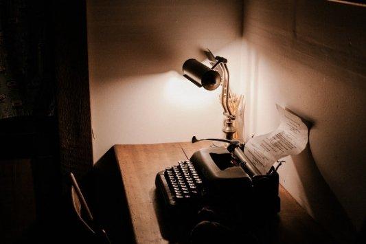 Vieja máquina de escribir con una luz de escritorio.