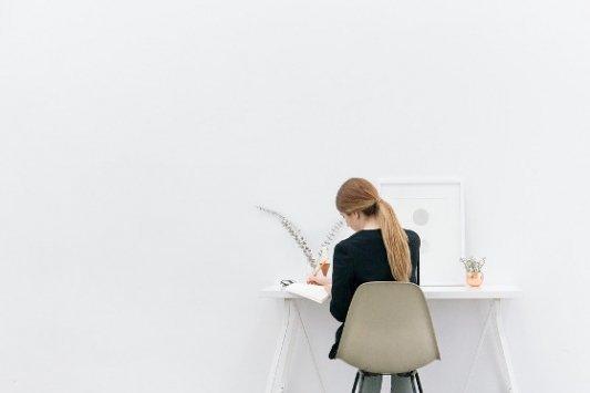 Mujer escribiendo en una habitación blanca.