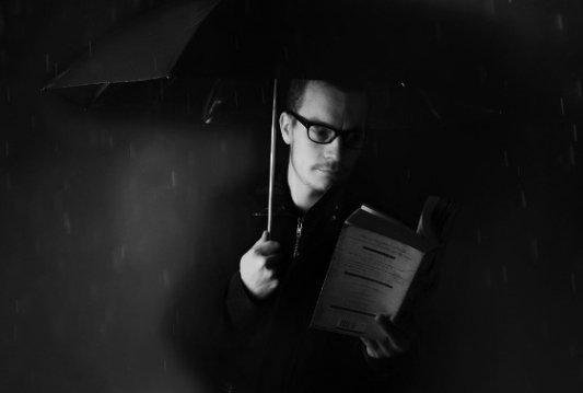 Hombre leyendo bajo la lluvia.