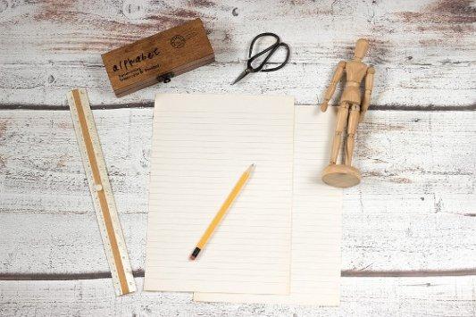 Papel, lápiz, tijeras, regla y un muñeco articulado.