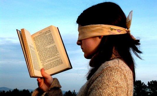 Chica leyendo con los ojos vendados.