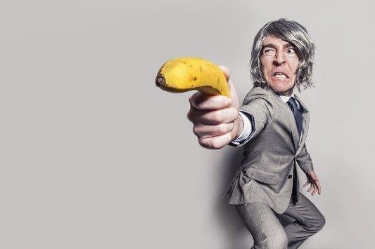 Personaje con traje empuñando un plátano como pistola.