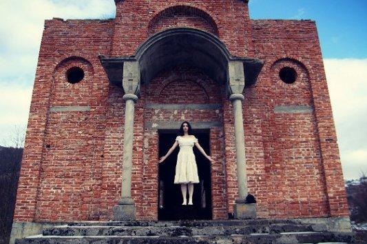 Fantasma de una chica frente a edificio en ruinas.