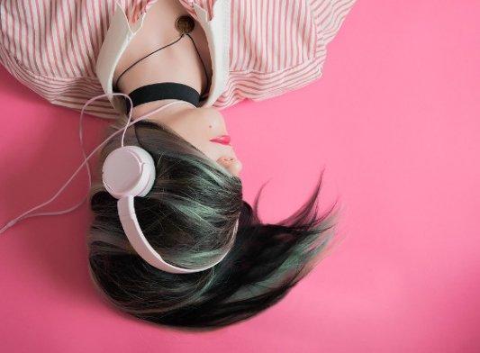 Chica con auriculares vestida de rosa y a la moda.