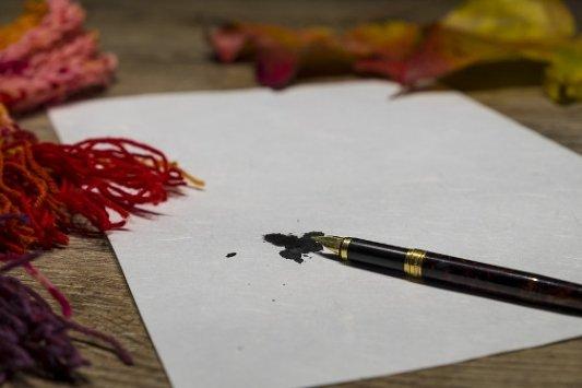 Pluma manchando de tinta una página en blanco.