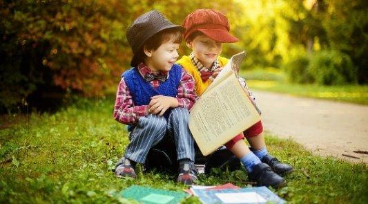 Dos niños pequeños leyendo un libro