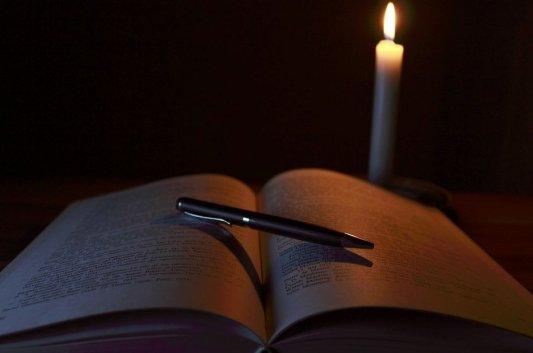 Libro abierto alumbrado por una vela